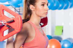 Portrait of a young pretty woman holding crossfit barbell and doing fitness indor. Crossfit hall. Gym shot. Royalty Free Stock Images