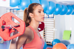 Portrait of a young pretty woman holding crossfit barbell and doing fitness indor. Crossfit hall. Gym shot. Royalty Free Stock Image