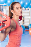 Portrait of a young pretty woman holding crossfit barbell and doing fitness indor. Crossfit hall. Gym shot. Royalty Free Stock Photography