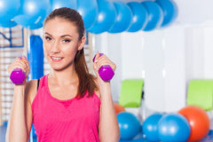 Portrait of a young pretty woman holding weights (dumbbell) and Royalty Free Stock Photos