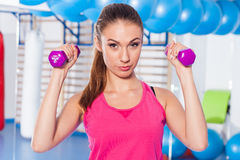 Portrait of a young pretty woman holding weights (dumbbell) and Stock Photo