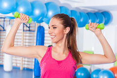 Portrait of a young pretty woman holding weights (dumbbell) and Royalty Free Stock Images
