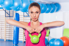 Portrait of a young pretty woman holding weights (dumbbell) and Stock Images
