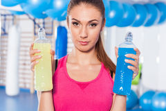 Portrait of a young pretty woman holding weights (dumbbell) and Stock Photography