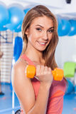 Portrait of a young pretty woman holding weights (dumbbell) and doing fitness indor. Crossfit hall. Gym shot. Stock Photography