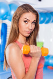 Portrait of a young pretty woman holding weights (dumbbell) and doing fitness indor. Crossfit hall. Gym shot. Royalty Free Stock Images