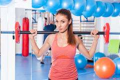 Portrait of a young pretty woman holding weights (dumbbell) and doing fitness indor. Crossfit hall. Gym shot. Royalty Free Stock Photo