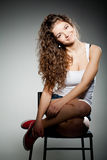 Portrait of young pretty woman sitting on chair Stock Photos