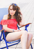 Portrait of young pretty woman sitting outdoors in sunny day Royalty Free Stock Photo