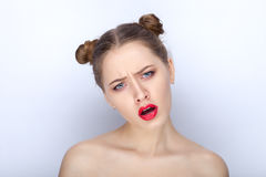 Portrait of a young pretty woman with trendy makeup bright red lips funny bun hairstyle and bare shoulders act the ape against whi. Te studio background Stock Photo
