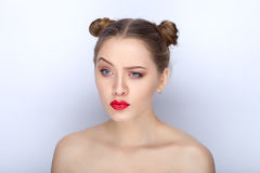 Portrait of a young pretty woman with trendy makeup bright red lips funny bun hairstyle and bare shoulders act the ape against whi. Portrait of a young pretty Stock Image