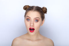 Portrait of a young pretty woman with trendy makeup bright red lips funny bun hairstyle and bare shoulders act the ape against whi. Portrait of a young pretty Royalty Free Stock Photography