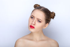 Portrait of a young pretty woman with trendy makeup bright red lips funny bun hairstyle and bare shoulders act the ape against whi Stock Photos