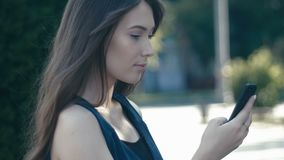 Portrait of young pretty woman using smartphone outdoor at street background. Portrait of a young pretty woman outdoor at street background stock video footage