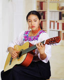 Portrait of young pretty woman wearing beautiful traditional andean clothing, sitting down with acoustic guitar playing Royalty Free Stock Photos