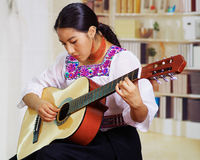 Portrait of young pretty woman wearing beautiful traditional andean clothing, sitting down with acoustic guitar playing Stock Photography