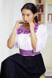 Portrait of young pretty woman wearing beautiful traditional andean clothing, sitting down with while playing the Royalty Free Stock Photo