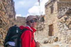 Portrait Young Pretty Woman Wearing Red Jacket Backpack Crossing Mountains Village.Mountain Trekking Rocks Path.Old Town Royalty Free Stock Photos