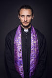 Portrait of young priest. Studio portrait on black background Royalty Free Stock Image