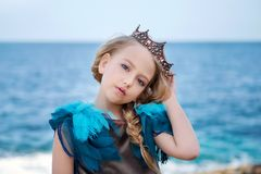 Portrait of a young princess girl in a crown and azure dress is tilted her head and looks tenderly. Portrait of a young princess girl in a crown and azure dress Royalty Free Stock Photos