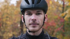Portrait of young professional cyclist in fall beautiful forest. Extra close up view of male face in helmet puts on sport glasses. Before cycling training stock footage