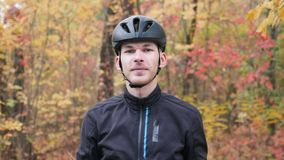 Portrait of young professional male cyclist in autumn park. Attractive smiling sportive guy taking off black helmet and glasses af. Ter training. Cycling stock video footage