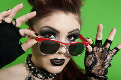 Portrait of young punk woman wearing sunglasses over green background Stock Photos