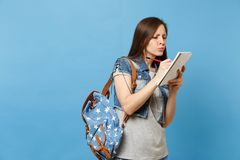 Portrait of young puzzled thoughtful woman student in grey t-shirt denim clothes with backpack taking exam writing on stock photos