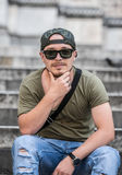 Portrait of a young rap guy. Portrait of a young guy dresses as a rapper with sunglasses a cool camouflage hat, jeans and nice stylish watch Stock Images