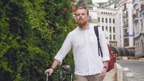 Portrait of young red bearded man walking to work with bicycle. Portrait of young bearded man walking to work with bicycle Royalty Free Stock Image