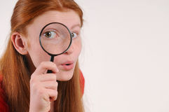 Portrait of a young red hair teen woman looking at the camera through a magnifying glass Stock Photo