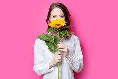 Portrait of young red-haired girl with sunflower. On pink background Royalty Free Stock Images