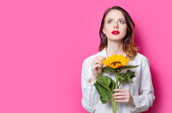 Portrait of young red-haired girl with sunflowers. On pink background Royalty Free Stock Photography