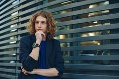 Portrait of red haired man over urban futuristic background. Portrait of young red haired, reddish man with curly hair, gray jacket, blue t-shirt and vintage Stock Photos