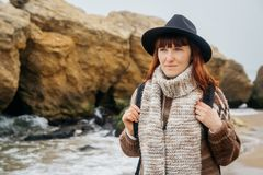 Portrait of a young red-haired woman in a hat and a scarf with a backpack against the background of the rocks against royalty free stock photo