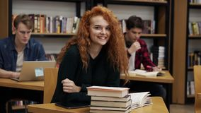 Portrait of a young red headed curly female student working on her thesis or preparing for exam. Reading a book sitting