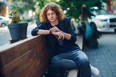 Red haired hipster man sitting on bench looking to his watch. Portrait young reddish, red haired man with curly hair in jacket and T-shirt, looking and touching Royalty Free Stock Images