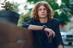 Red haired hipster man sitting on bench with coffe to go. Portrait young reddish, red haired man with curly hair, vintage watch, jacket and T-shirt, holding a Stock Images