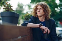 Red haired hipster man sitting on bench thinking. Portrait young reddish, red haired man with curly hair, vintage watch, jacket and T-shirt, holding a coffee to Royalty Free Stock Images