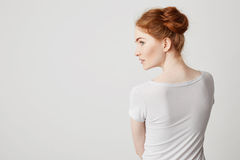 Portrait of young redhead girl with buns standing back to camera looking in side over white background. Copy space Stock Image