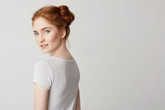 Portrait of young redhead girl with buns standing back turning and looking to camera over white background. Stock Photo
