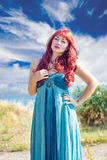 Portrait of a young redhead girl. Portrait of a young red-haired girl on a background of sky and river Stock Photography