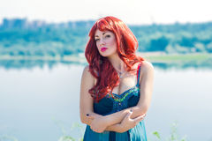 Portrait of a young redhead girl. Portrait of a young red-haired girl on a background of sky and river Stock Photos