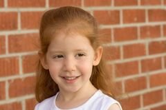 Portrait of Young redhead kid girl by brick wall. Portrait of Young smiling redhead kid girl by brick wall Royalty Free Stock Images