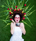 Portrait of a young redhead woman with camera and tulips Royalty Free Stock Photography