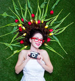 Portrait of a young redhead woman with camera and tulips Royalty Free Stock Image