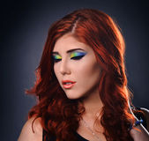 Portrait of a young redhead woman with colorful make up. Studio Portrait of a young redhead woman with colorful make up isolated over gray Royalty Free Stock Photography
