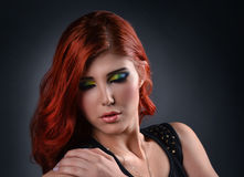 Portrait of a young redhead woman with colorful make up. Studio Portrait of a young redhead woman with colorful make up isolated over gray Royalty Free Stock Photos
