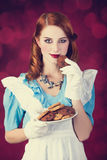 Portrait of a young redhead woman. Dressed as Alice in Wonderland, video game stock image