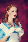 Portrait of a young redhead woman. Dressed as Alice in Wonderland, video game stock photos
